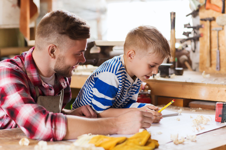 woodwork: family, carpentry, woodwork and people concept - happy father and little son with blueprint at workshop Stock Photo