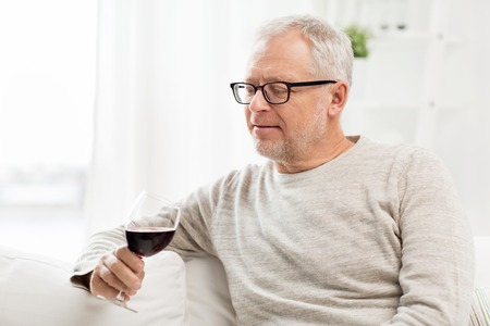 degustating: people, alcohol and drinks concept - senior man drinking red wine from glass at home