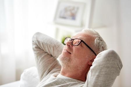 vecchiaia: la vecchiaia, il comfort e la gente concept - sorridente uomo anziano con gli occhiali di relax sul divano di casa Archivio Fotografico