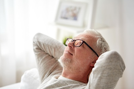age old: old age, comfort and people concept - smiling senior man in glasses relaxing on sofa at home