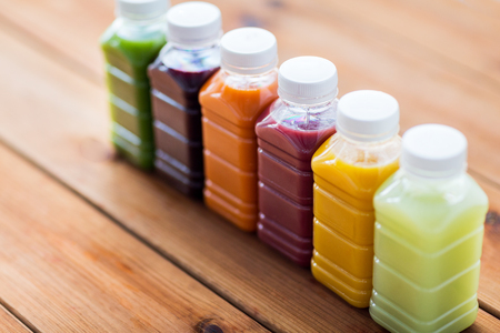 healthy eating, drinks, dieting and packaging concept - plastic bottles with different fruit or vegetable juices on wooden table Stock Photo - 64886137