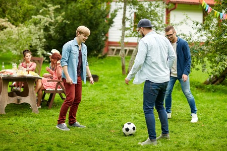boyfriends: leisure, holidays, people and sport concept - happy friends playing football at summer garden party