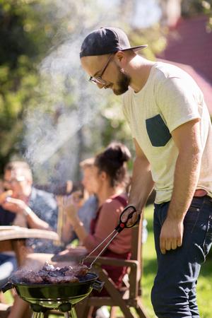 vrije tijd, voedsel, mensen en vakantieconcept - mensen kokend vlees bij de barbecuegrill voor zijn vrienden bij de zomer openluchtpartij