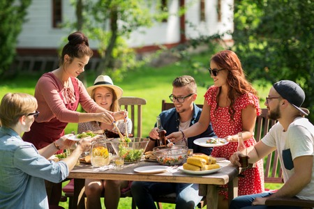 holiday gathering: leisure, holidays, eating, people and food concept - happy friends having dinner and sharing salad at summer garden party