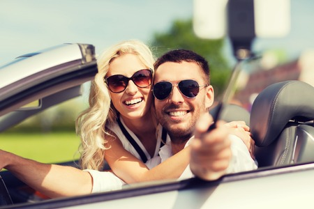 driving a car: road trip, leisure, couple, technology and people concept - happy man and woman driving in cabriolet car and taking picture with smartphone on selfie stick Stock Photo