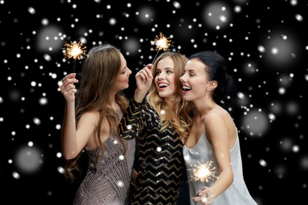party background: new year party, christmas, winter holidays and people concept - happy young women with sparklers over black background with snow