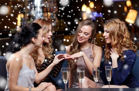 verlobung: weihnachten, Freunde, Bachelorette Party und Winterferien Konzept - glückliche Frau Verlobungsring zu ihren Freunden mit Champagner Gläser im Nachtclub auf Schnee zeigen Lizenzfreie Bilder