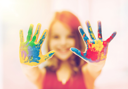 painted: education, art, people, childhood and drawing concept - little happy student girl showing painted hands Stock Photo