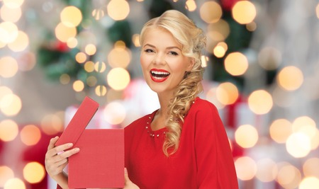 navidad elegante: christmas, holidays, celebration and people concept - smiling woman in red dress with gift box over lights background