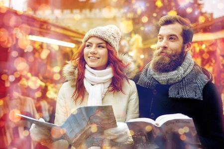 vacances, hiver, noël, le tourisme et les gens notion - heureux couple dans des vêtements chauds avec carte et guide de la ville dans la vieille ville