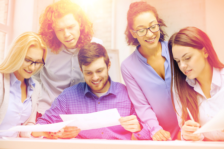 business, office and startup concep - smiling creative team with papers working in office photo
