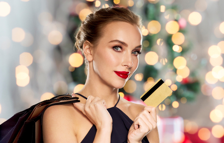 prosperidad: people, luxury, holidays and sale concept - beautiful woman with credit card and shopping bags over christmas tree lights background