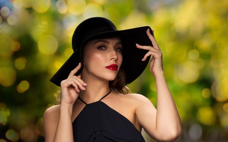 femme fatale: people, luxury, holidays and fashion concept - beautiful woman in black hat over green lights background