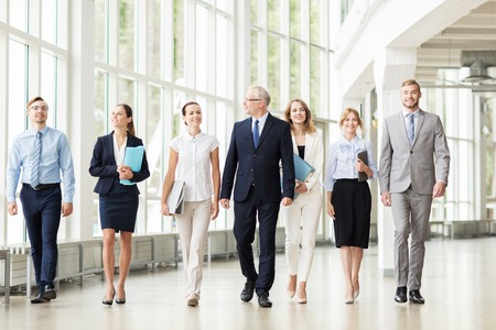 business partners: people, work and corporate concept - business team with folders walking along office building and talking