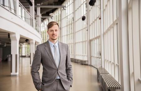 business, corporate and people concept - young businessman in suit at office building hall