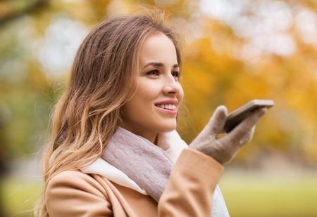 temporada, la tecnología y el concepto de la gente - hermosa mujer joven que recorre en parque del otoño y el uso de la grabadora de comandos de voz en el teléfono inteligente Foto de archivo
