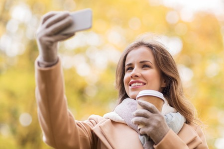 tomando refresco: season, technology and people concept - beautiful young happy woman taking selfie with smartphone in autumn park