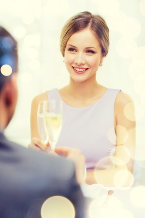 familia cenando: restaurant, couple and holiday concept - smiling woman with glass of champagne looking at husband or boyfriend at restaurant