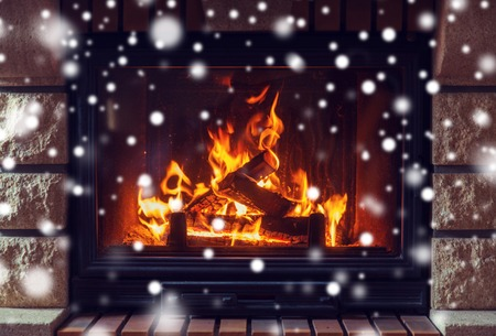 hotbed: winter, christmas, warmth, fire and coziness concept - close up of burning fireplace at home with snow