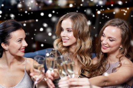 party night: celebration, friends, new year, christmas and winter holidays concept - happy women with champagne glasses at bachelorette party at night club over snow