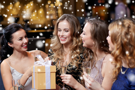 party friends: celebration, friends, new year, christmas and winter holidays concept - happy women with champagne glasses and gift box at bachelorette or birthday party at night club over snow Stock Photo