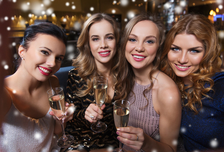 night out: friends, bachelorette party, technology and holidays concept - happy smiling young pretty women with champagne glasses taking selfie at night club