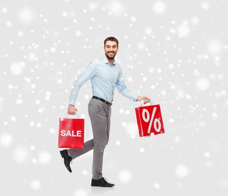 percentage sign: people, sale, christmas, winter and holidays concept - smiling man holding red shopping bags with percentage sign over snow background