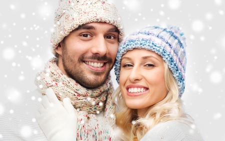 christmas hats: winter, fashion, couple, christmas and people concept - smiling man and woman in hats and scarf hugging