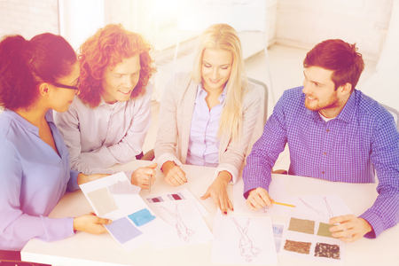 business, office, clothes design and starup concept - smiling creative team looking at sketch photo