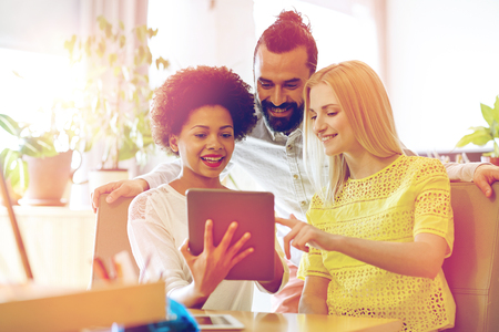 Wirtschaft, Technik, Inbetriebnahme und Menschen Konzept - glücklich kreatives Team mit Tablette-PC-Computer im Büro