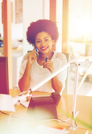 application university: business, startup and people concept - happy african american businesswoman or creative worker calling on smartphone at office
