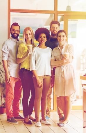 multiracial: business, startup, people, drinks and teamwork concept - happy smiling international creative team with disposable paper coffee cups in office