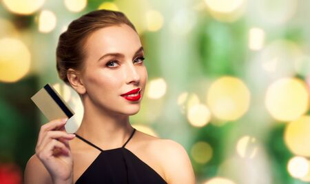 femme fatale: people, luxury, christmas, finances and shopping concept - beautiful woman with credit card over holidays lights background Stock Photo