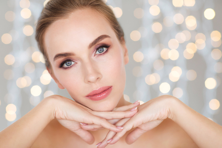 smile face: beauty, people and bodycare concept - beautiful young woman face and hands over holidays lights background Stock Photo