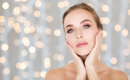 Krása, lidé a zdraví koncepce - krásná mladá žena se dotýká její tvář přes prázdniny světla pozadí Reklamní fotografie