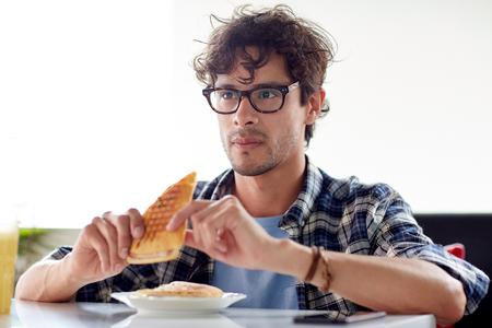 hombre comiendo: ocio, alimentación, la alimentación y el concepto de la gente - hombre feliz comiendo sándwich en el café para el almuerzo Foto de archivo