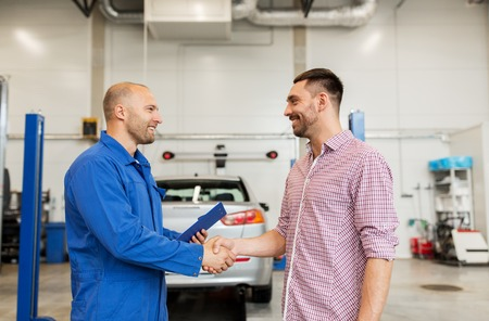 auto service, repair, maintenance, gesture and people concept - mechanic with clipboard and man or owner shaking hands at car shop