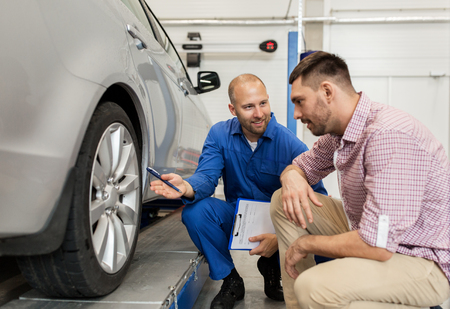 auto service, repair, maintenance and people concept - mechanic with clipboard showing tire to man or owner at car shop Zdjęcie Seryjne