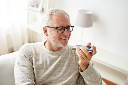 using voice: technology, people, lifestyle and communication concept - of happy senior man using voice command recorder or calling on smartphone at home