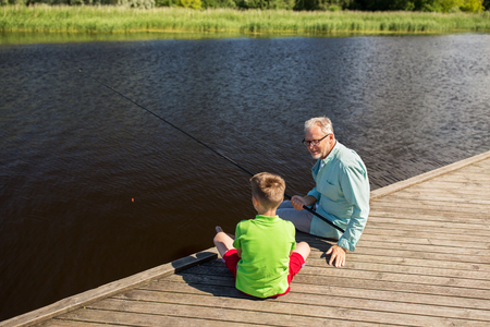 fishman: family, generation, summer holidays and people concept - happy grandfather and grandson with fishing rods on river berth
