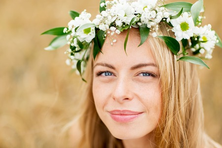 campo de flores: nature, summer holidays, vacation and people concept - face of happy woman in wreath of flowers Foto de archivo