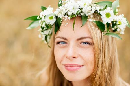 champ de fleurs: Nature, vacances d'été, vacances et concept de personne - visage de femme heureuse dans une couronne de fleurs Banque d'images