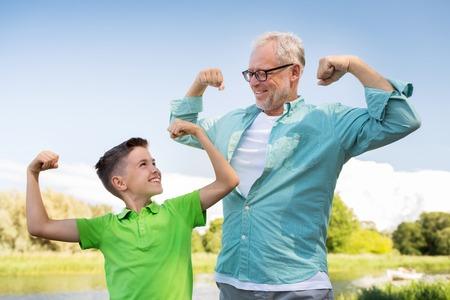 家族、世代、力、人のコンセプト - 幸せな祖父と孫の筋肉を示す