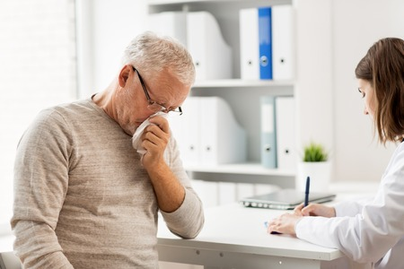 medicine, age, health care, flu and people concept - senior man blowing nose with napkin and doctor with clipboard writing at medical office at hospital