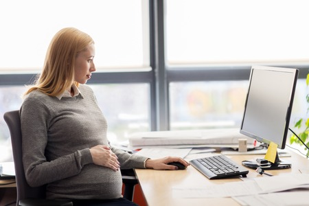 pregnancy, business, work and technology concept - pregnant businesswoman with computer sitting at office table