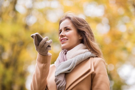using voice: season, technology and people concept - beautiful young woman in autumn park and using voice command recorder on smartphone