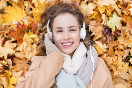 season, technology and people concept - beautiful happy young woman with headphones lying on autumn leaves listening to music
