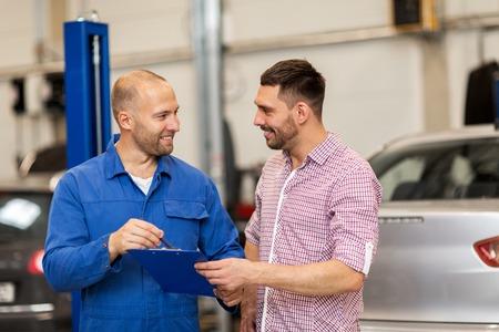 auto-service, reparatie, onderhoud en mensen concept - monteur met klembord praten met man of eigenaar op de auto winkel