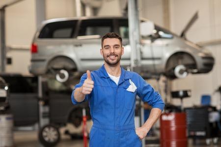 Autoservice-, Reparatur-, Wartungs-, Gesten- und Leutekonzept - glücklicher lächelnder Automechanikermann oder -schmied, die sich Daumen an der Werkstatt zeigen Standard-Bild - 65060878