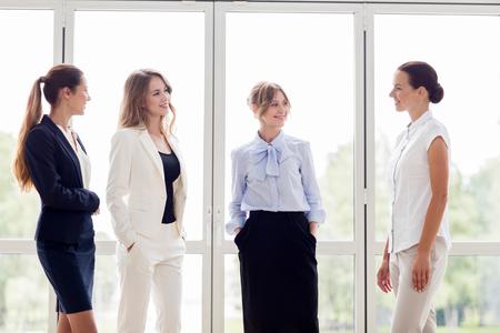 gente, el trabajo y el concepto empresarial - mujeres de negocios reunidos en la oficina y hablar